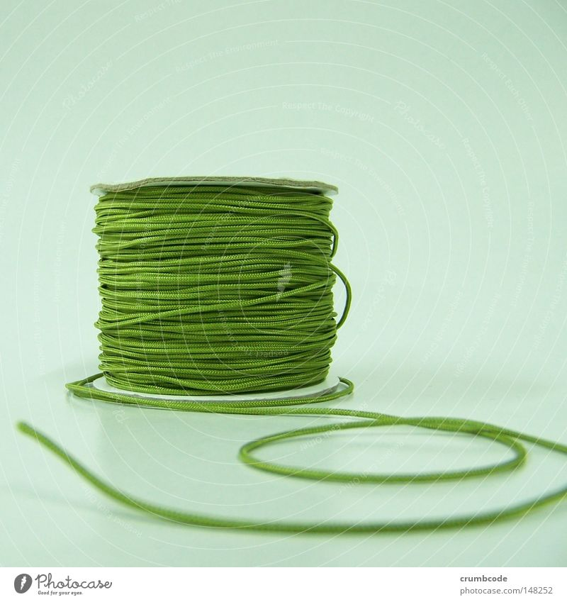 off the roll Craft (trade) Green Wound up Coil Product photography Things Sewing thread Close-up Still Life Deserted Studio shot Handcrafts String