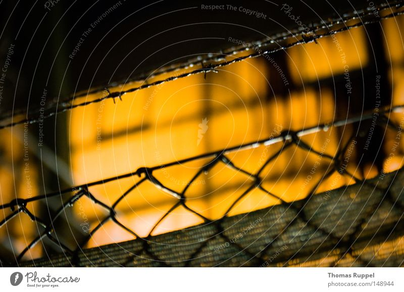 fence Warehouse Hall Blur Large Lighting Fence Tall Wire Thorny Wire netting fence Pattern Barbed wire Building Orange Dark Narrow Loneliness Border Limitation