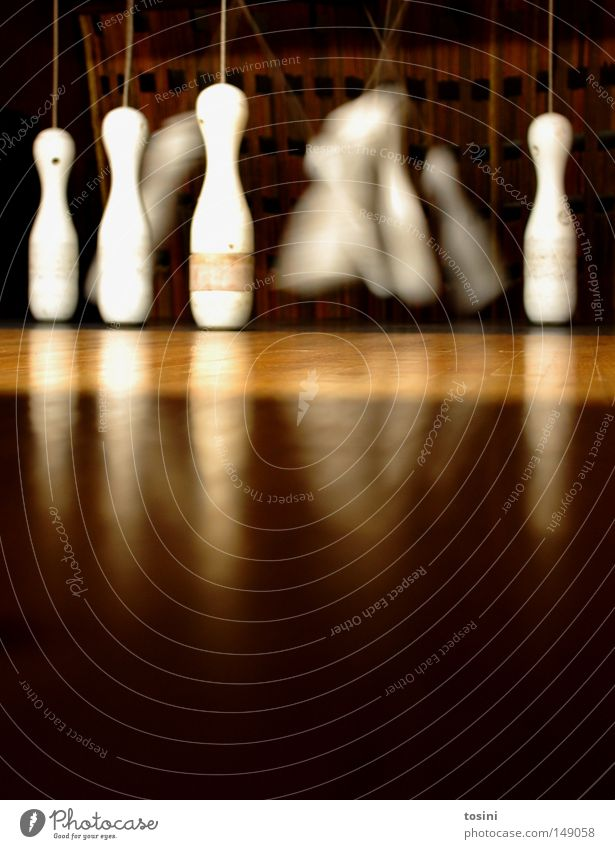 four left Nine-pin bowling Location Floor covering Ground Worm's-eye view Conical Skittle Sphere Tumble down Wood Brown Bowling Sports Sporting event Swing