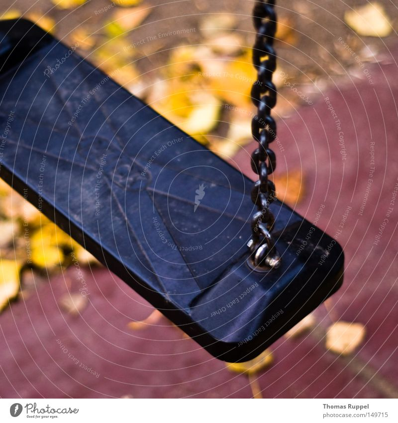 Standstill on the playground Swing Dark Gray Black Playground Deserted Chain Leaf Blur Yellow Autumn Toys Infancy Playing Joy Exterior shot