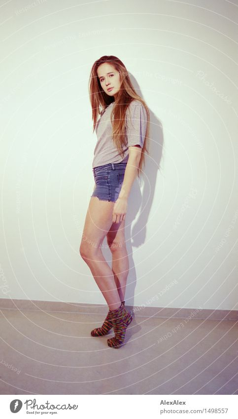 Young athletic woman with long legs stands sideways in front of white wall and looks into camera Style Athletic Well-being Young woman Youth (Young adults) Face