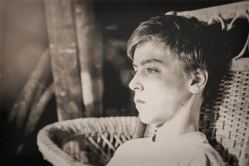 Black and white picture of a teenager in a wicker chair Lifestyle Style Design pretty Senses Relaxation Calm Attic Human being Masculine Young man