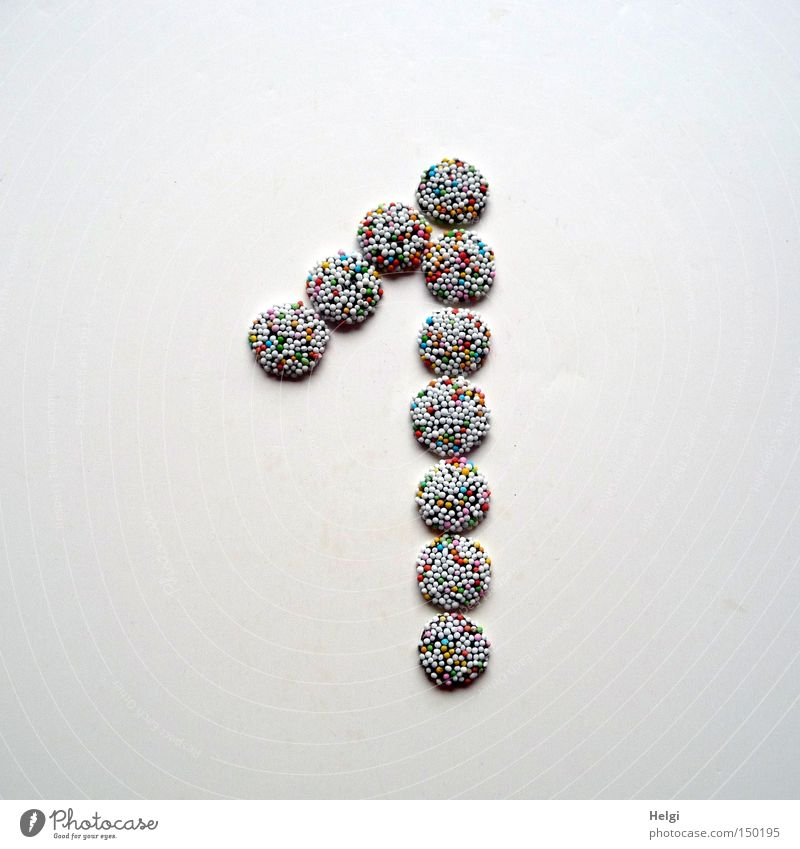 Number 1 of small chocolate candies with colored sugar sprinkles on a white background Digits and numbers Advent Calendar Door Candy Chocolate Granules