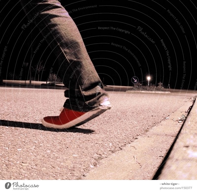 nightly walking Clothing Pants Jeans Footwear Signs and labeling Red Pavement Asphalt Curbside Street refuge Colour photo Exterior shot Night Shadow Going