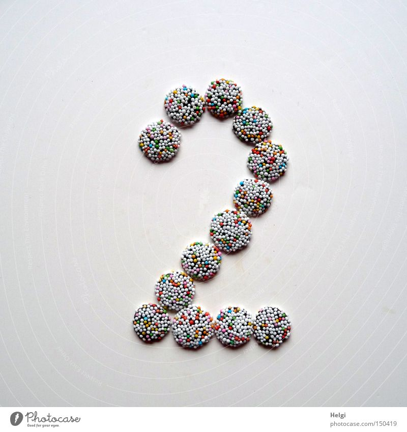 Number 2 laid out of small chocolate candies with colored sugar sprinkles on white background Digits and numbers Advent Calendar Candy Chocolate Granules