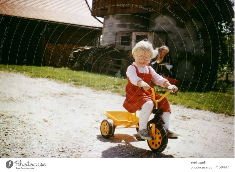Wheels keep on turning... Yellow Red Tricycle Child Blonde Driving Farm Courtyard Eyeglasses Dress Joy Toddler Summer