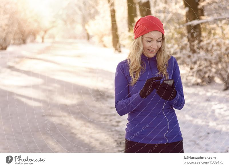 Woman checking her mobile phone Human being Winter Face Adults Lanes & trails Lifestyle Business Park Copy Space Blonde Fitness Telephone Information Text PDA