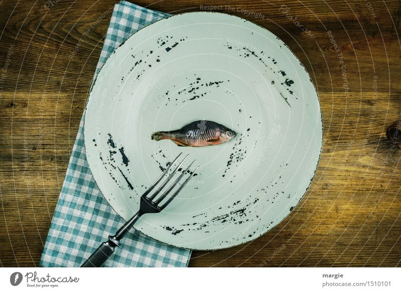 A plate with a small fish on it, a fork, a napkin on a wooden table Food Fish Nutrition Lunch Organic produce Diet Fasting Plate Fork Healthy Cook Animal