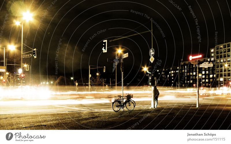 Man stands next to bicycle at night at Berlin crossroads with traffic Town Transport Traffic infrastructure Street Crossroads Road junction Traffic light Car