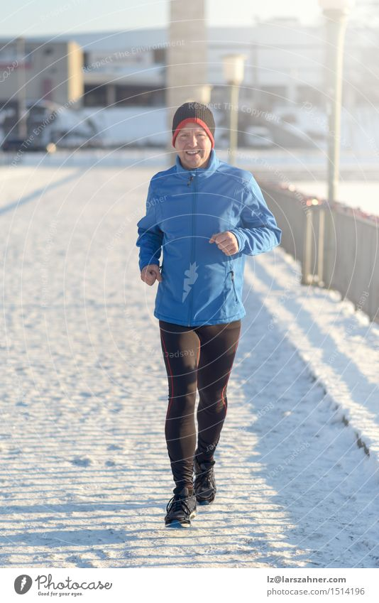 Man jogging in winter clothing Lifestyle Face Winter Snow Sports Jogging Adults 30 - 45 years Newspaper Magazine Park Street Fitness Determination Action