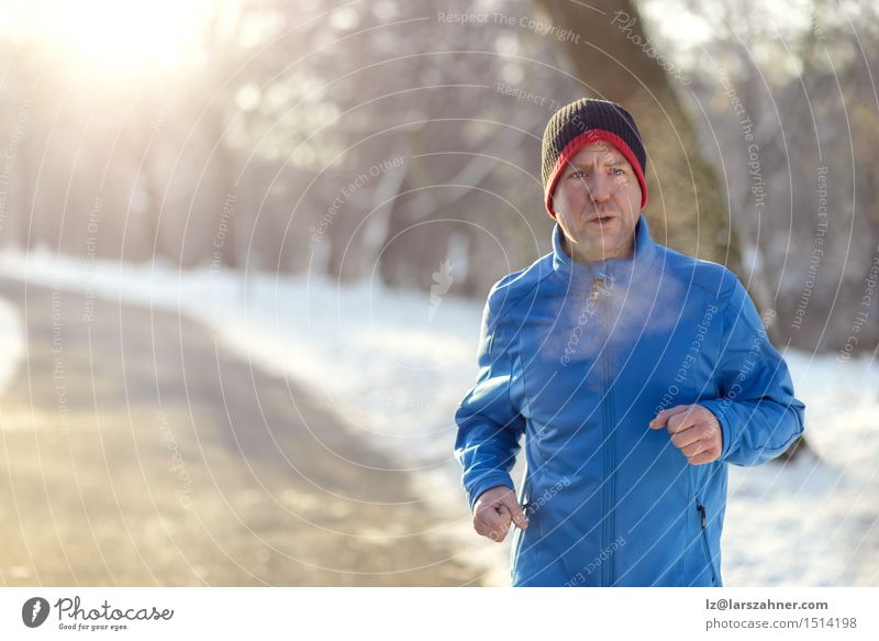 Man jogging in winter clothing Man Winter Face Adults Street Snow Sports Lifestyle Park Copy Space Action Fitness Middle Newspaper Breathe Guy
