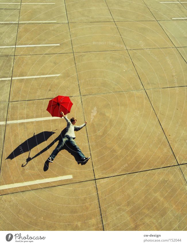 Human being Man Red Joy Playing Masculine Concrete Stand Lie Umbrella Sunshade Traffic infrastructure Beautiful weather Umbrellas & Shades Parking lot