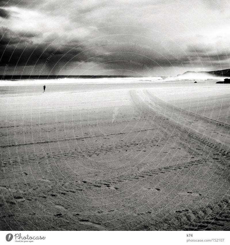 rain Sky Weather Clouds Tracks Coast Beach Ocean Human being Jogger Rain Gale Skid marks Surf Black & white photo