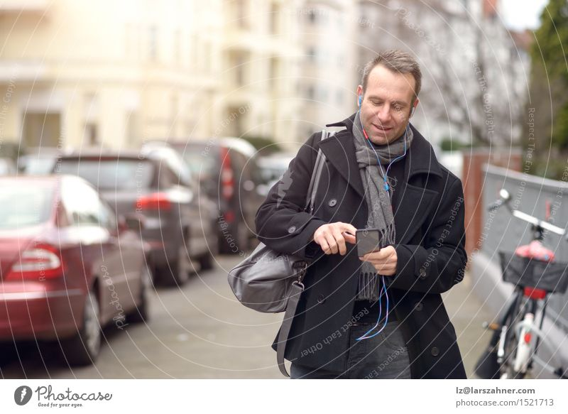 Attractive man in winter fashion checking his mobile Human being Man Winter Adults Street To talk Fashion Business Masculine Copy Space Technology Smiling