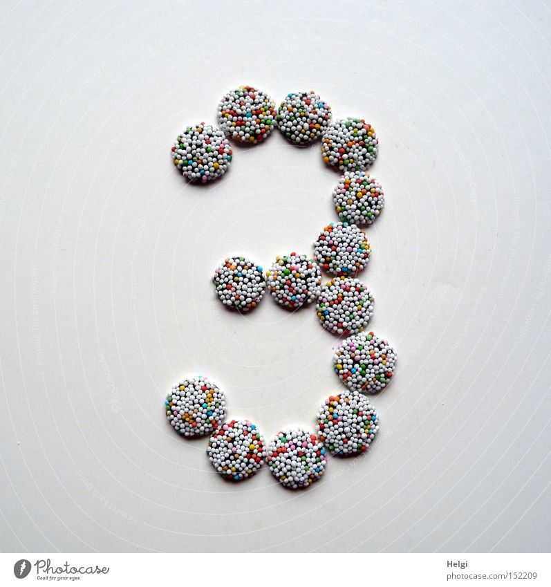 Number 3 laid out of small chocolate candies with colored sugar sprinkles on white background Digits and numbers Advent Calendar Candy Chocolate Granules
