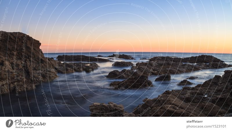 Long exposure of sunset over rocks Vacation & Travel Success Earth Air Water Coast Ocean Stone Blue Brown Yellow Orange Pink Loneliness Destruction Colour photo