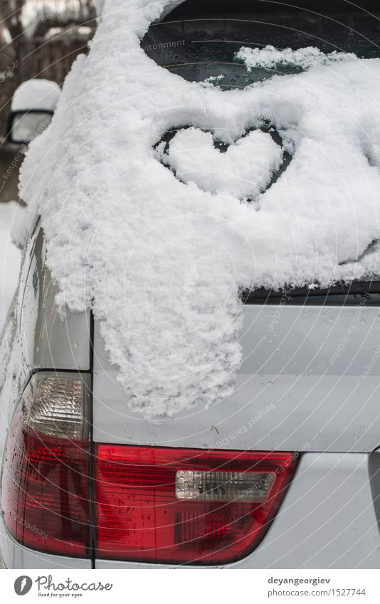 Snow heart shape on car. Winter Car Heart Love Happiness White Romance ice cold Symbols and metaphors Frost romantic window drawing background glass Frozen