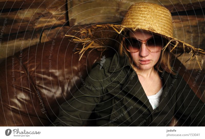 Woman Human being Face Sit Might Cool (slang) Leather Sunglasses Armchair Wooden wall Mistrust Hat Straw hat Hard-nosed