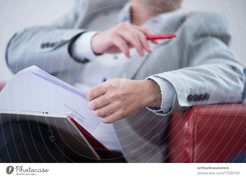 Businessman in a suit with documents in his hand on a red couch Professional training Academic studies Study Office work Workplace Economy Services