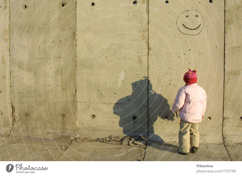 Smile! Grief Happiness Smiley Wall (barrier) Wall (building) Child Defiant Shadow Graffiti Beautiful weather Timidity Fear Concrete Sadness