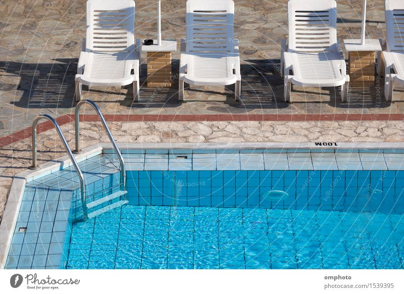 Clean blue swimming pool with clear water and sunbeds around it in a hot summer morning. Lifestyle Beautiful Relaxation Spa Swimming pool Swimming & Bathing