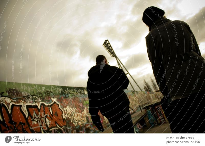 togetherness Human being Woman Man Sky Dark Clouds Threat Wall (barrier) Town Graffiti Graphite Shadow Silhouette To go for a walk Far-off places Berlin