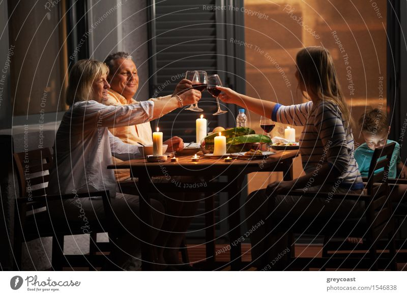 Family dinner outdoor in the backyard in quiet evening. Young woman and senior parents toasting with wine while child playing games Vegetable Dinner