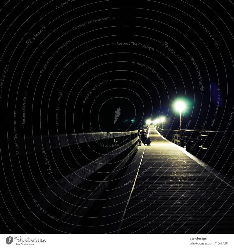 Human being Loneliness Cold Dark Sit Wait Bridge Lantern Night Feeble Crouch Flare Sea bridge Cone of light Nocturnal ramble Wooden bridge