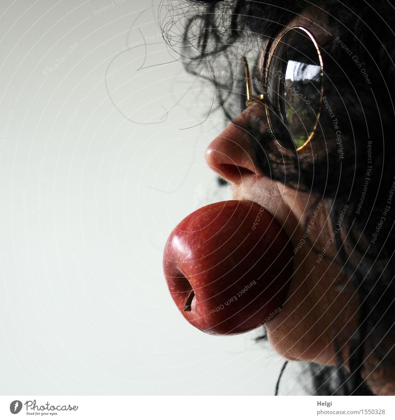 Close up of a female face with sunglasses and black hair and a whole apple in her mouth Food Apple Organic produce Human being Feminine Woman Adults