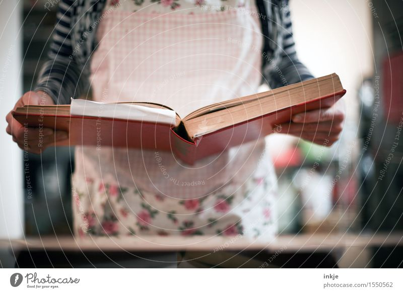 The baking book. Nutrition Cookbook Lifestyle Leisure and hobbies Woman Adults Body Hand 1 Human being Apron Book Reading Housewife recipe Mother Cliche