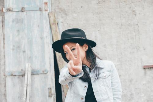 peekaboo Black-haired Long-haired Cool (slang) Authentic Free Happiness Happy Funny Hat Jeans jacket Tourist Vacation & Travel Discover Barn Hide Peace Sign