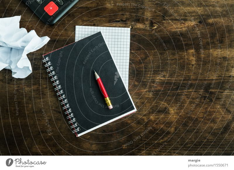 """a red pencil on a black notebook, a plaid piece of paper, a white crumpled sheet with a red """"+"""" on an old desk School Professional training Academic studies"""