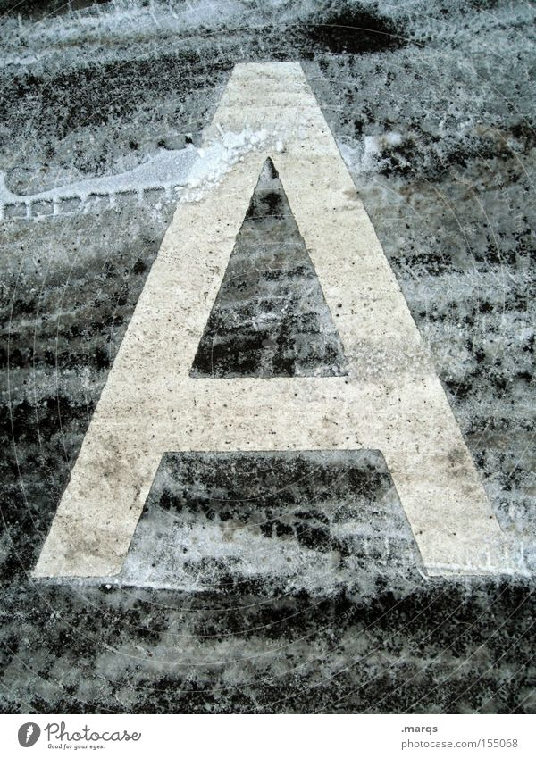 a Colour photo Subdued colour Exterior shot Detail Winter Snow Street Concrete Characters Cold Tracks Typography Asphalt Frozen Latin alphabet