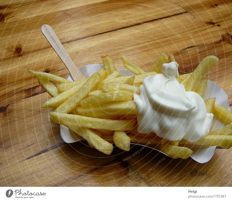 portion of French fries with mayonnaise in a cardboard bowl and a wooden fork on a wooden table Colour photo Exterior shot Copy Space top Food Nutrition