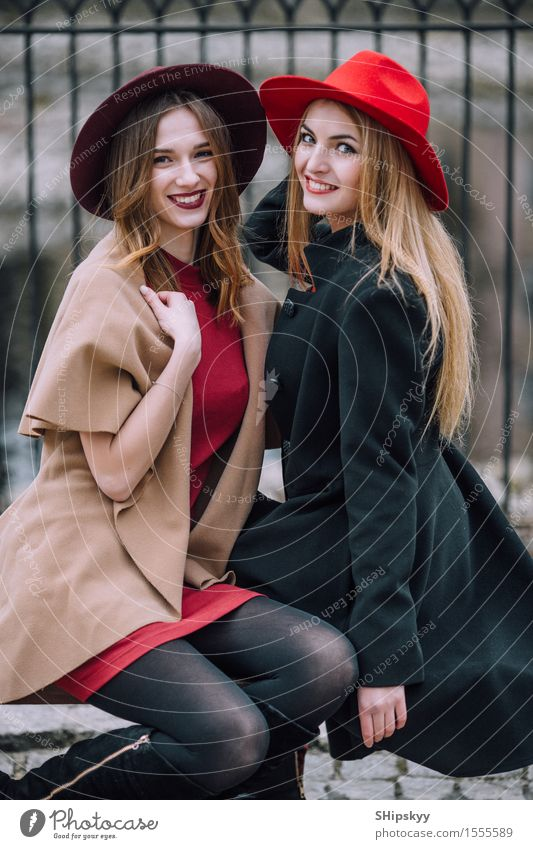 Two girls sitting on the bench and smile Lifestyle Joy Happy Beautiful Face Meeting To talk Human being Feminine Woman Adults Friendship Autumn Fashion Hat