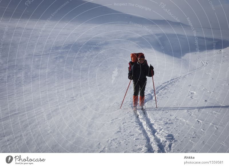 Young female skier in a wintery mountain landscape with a large backpack in orange colours Adventure Far-off places Freedom Snow Winter vacation Skiing Feminine