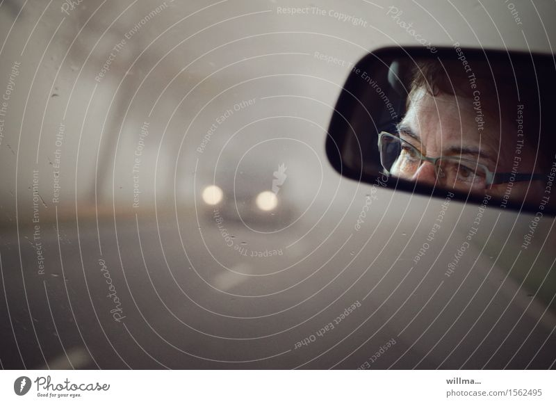 Driving in fog, woman with glasses seen in rear view mirror Fog Motoring Street fog lamps Floodlight Rear view mirror Caution Concentrate Watchfulness