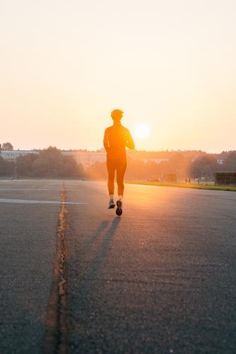 Woman jogging into a sunrise Body Healthy Athletic Fitness Contentment Adventure Summer Sun Sunbathing Sports Sports Training Jogging Human being Feminine