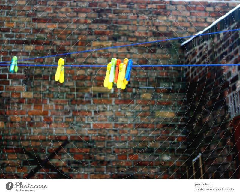 Colorful clothes pegs are hanging from a clothesline in a backyard. Budget Courtyard House (Residential Structure) Brick Wall (barrier) Clothes peg Household