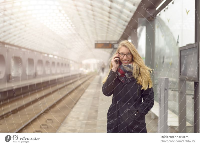 Young woman in black coat using mobile phone Human being Woman Youth (Young adults) Winter 18 - 30 years Face Adults Feminine Happy Transport Blonde Authentic Happiness Stand Smiling Railroad