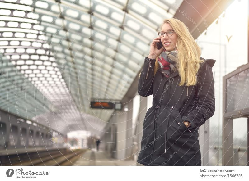 Blond woman with mobile phone at train station Happy Face Winter Telephone PDA Feminine Woman Adults 1 Human being 18 - 30 years Youth (Young adults) Transport
