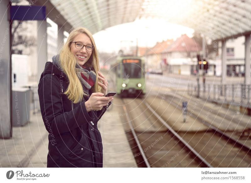 Smiling young woman in black coat, blond hair and eyeglasses standing at station Happy Vacation & Travel Winter Telephone Woman Adults Transport Railroad Blonde
