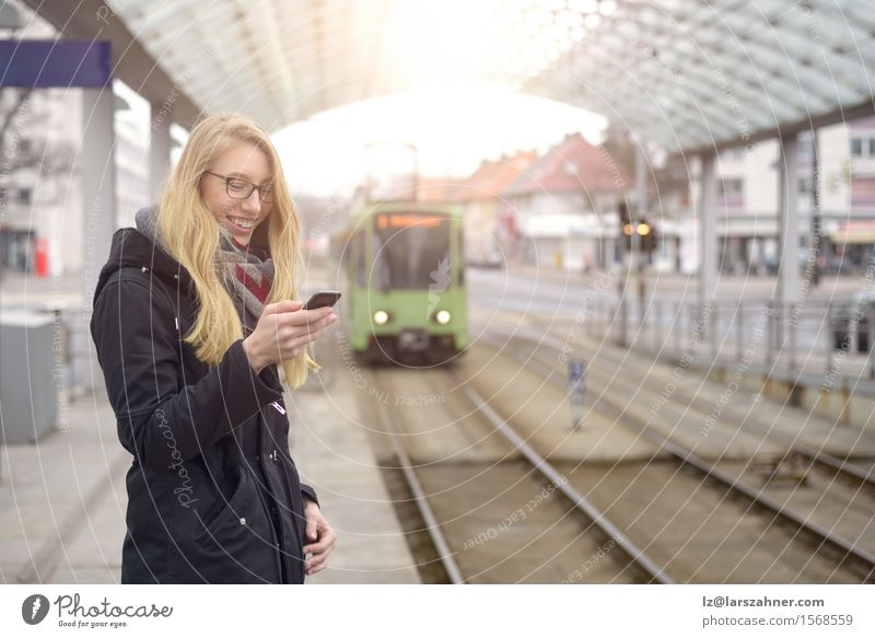 Young woman with mobile phone at train station Happy Vacation & Travel Winter Telephone Woman Adults 1 Human being 18 - 30 years Youth (Young adults) Transport
