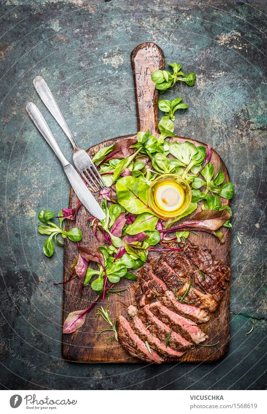Grilled steak with green salad and cutlery on cutting board Food Fish Lettuce Salad Herbs and spices Cooking oil Nutrition Lunch Dinner Picnic Organic produce