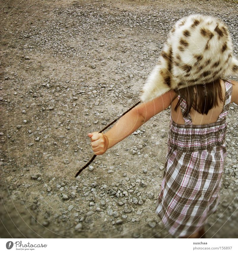 child on gravel with fur cap ... what else ... Child Girl Dress Summer Warmth Winter Gravel Playing Joy Style Strange Whimsical Freedom Infancy Parenting