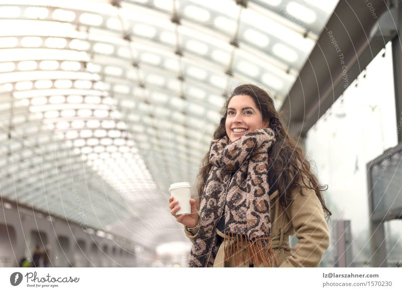 Smiling brown in winter coat holding a cup of coffee Human being Woman Youth (Young adults) Winter 18 - 30 years Face Adults Happy Transport Copy Space