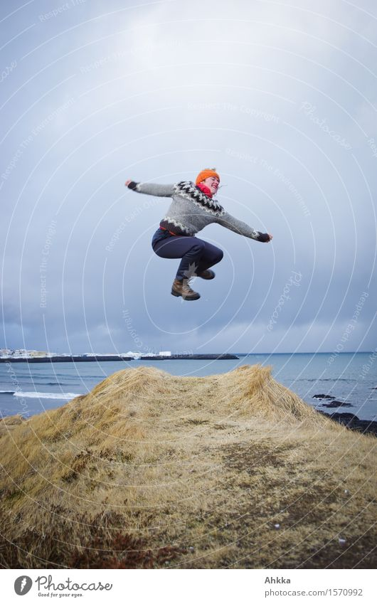 Jump from a cliff in wintry Iceland with view to the sea Life Well-being Contentment Trip Adventure Human being Young woman Youth (Young adults) 1 Landscape