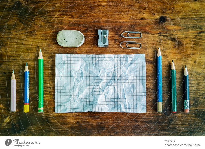 Notes and pencils, eraser, sharpener and paper clips on an old wooden table Education School Study Professional training Work and employment Office work