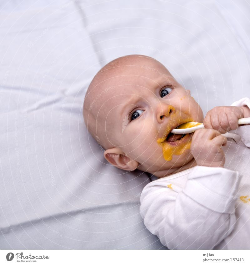 Hit rate. Baby Puree Nutrition Spoon White Portrait photograph Mouth Hand Daub Eating Child's portrait Face of a child Bright background Isolated Image Lie