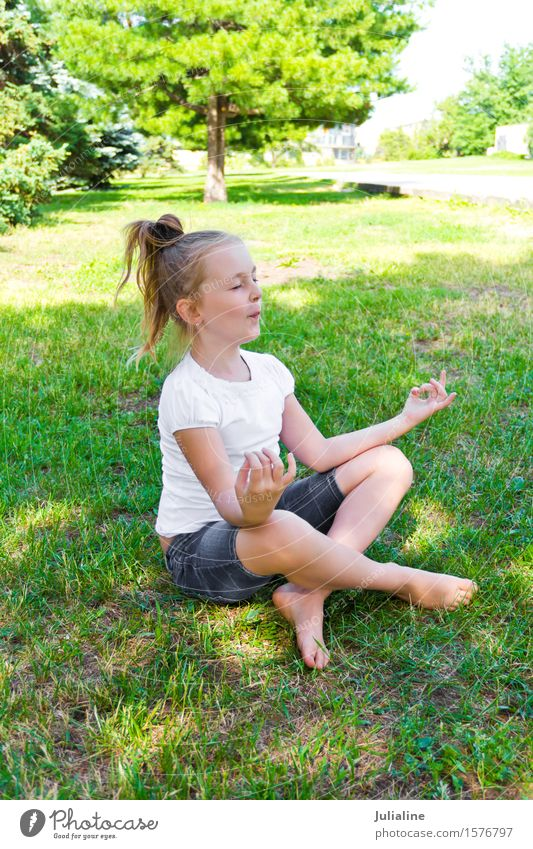 Cute girl are sitting on green grass Summer Yoga Child Schoolchild Girl Infancy 8 - 13 years Grass Blonde Blue Green White Lotus pose kid preschooler six 7